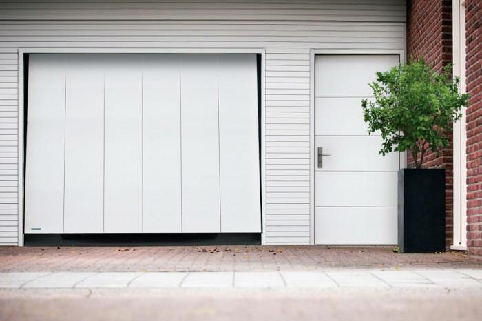 Moderní výklopná vrata a vedlejší dveře ve stejném designu.